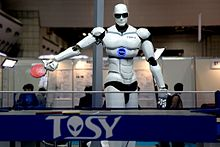 Photograph of a TOPIO humanoid ping-pong-playing robot