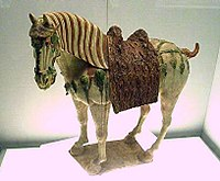 A Chinese Tang Dynasty tri-color glazed porcelain horse (ca. 700 CE), using yellow, green and white colors.
