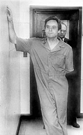 Bundy casually leans on the wall while dressed in prison garb.