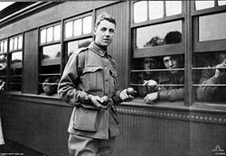 A young man in military uniform holding something in his hands stands beside a train carriage that has men looking out.