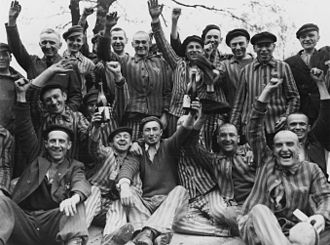 Priest Barracks of Dachau Concentration Camp - Polish prisoners in Dachau toast their liberation from the camp. Poles constituted the largest ethnic group in the camp and the largest proportion of those imprisoned in the Priest Barracks of Dachau.