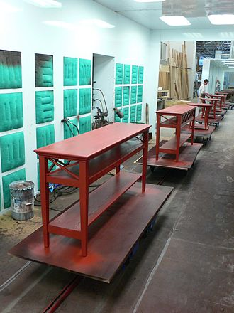 Wood finishing - In this Towline method, mobile carts move large furniture through various finishing stages on a conveyor system.