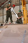U.S. Marine Corps Cpl. Wilfred R. Racela and Lance Cpl. Jason Raybueno, both airframe mechanics with Marine Attack Squadron (VMA) 211, prepare to replace the wings of an AV-8B Harrier II aircraft at Camp Bastion 120903-M-EF955-030.jpg