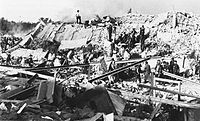 black-and-white image of men digging through rubble