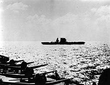 Le pont d'envol d'un porte-avions avec plusieurs avions se trouve au premier plan dans le coin gauche. À l'arrière-plan, on peut voir le profil d'un porte-avions