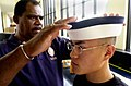 US Navy 030701-N-0399H-102 Officer candidate Byron Chen is fitted for a Plebe cover, at the U.S. Naval Academy (USNA) during induction day 2003.jpg