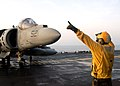 "US Navy 040803-N-8590P-022 Landing Signal Enlisted (LSE), Airman Hector Peralta helps direct an AV-8B Harrier assigned to the ""Fighting Griffins"" of Marine Helicopter Medium Squadron Two Six Six HMM-266 to land.jpg"