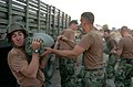 US Navy 040823-N-9712C-004 Seabees assigned to Naval Mobile Construction Battalion Four Zero (NMCB-40) load sandbags onto a vehicle for transport.jpg