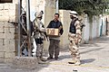 US Navy 041116-M-8096K-034 The Iraqi National Guard and U.S. Marines, assigned to Regimental-sized Combined Arms Team Seven (RCT-7) 1-3 Charlie Company, help pass out food and water to a civilian in the city of Fallujah, Iraq.jpg