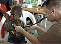 US Navy 070810-N-4267W-016 Lt. David King from Naval Medical Center San Diego, examines a child during a medical civil-assistance program (MEDCAP) at Josephstaal Medical Clinic.jpg