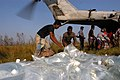 US Navy 071127-N-5642P-169 People of Doblarchar help unload bags of fresh water from a CH-53.jpg