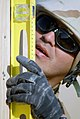 US Navy 071229-N-0553R-004 Builder 2nd Class Dennis Ortega assigned to Naval Mobile Construction Battalion (NMCB) 1, levels a recently erected wall.jpg
