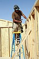 US Navy 081006-N-9623R-070 Builder 1st Class Thomas Henri works constructing the wall on a South West Asia hut.jpg