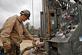 US Navy 090211-N-3674H-035 Construction Mechanic 3rd Class Trevor Schultz, assigned to Naval Mobile Construction Battalion (NMCB) 74, measures the water flow from a freshly drilled water well.jpg