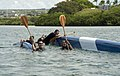 US Navy 100630-N-7200S-110 Sailors from the Republic of Singapore Navy frigate RSS Supreme (70) hang on their overturned outrigger canoe on the last turn of a Rim of the Pacific (RIMPAC) 2010 outrigger canoe race.jpg