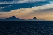 Sopky Shishaldin, Isanotski a Roundtop při pohledu z průsmyku Unimak v ranním světle.