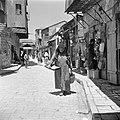 Vrouw met een dienblad met broodjes, lopend in een winkelstraat, vermoedelijk in, Bestanddeelnr 255-0373.jpg