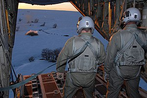2006 Colorado Holiday Blizzards - Wyoming Air National Guard loadmasters aboard a C-130 Hercules aircraft watch as a 1-ton hay bale lands near a herd of cows during an emergency feeding mission in southeast Colorado Jan. 3.