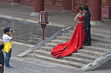 A woman wearing a long, ornate red dress stands next to a man in a black suit on some short stone steps while another man photographs them from the foot of the stairs