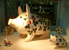 A large pig with comical features sits among other items in a shop display.