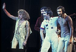 The Who onstage, standing and waving to a crowd