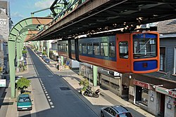 A train hanging from the rail runs above Sonnborner Straße.