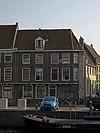 foto van Pand met overkraagde verdieping, aangebouwd tegen de buitenkant van de middeleeuwse stadsmuur
