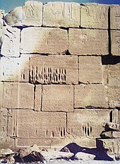 A stone wall that has eroded so that the joints between blocks are exposed. The blocks have straight edges but uneven shapes.
