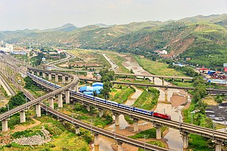 Taiyuan–Zhongwei–Yinchuan railway - A T70 passenger train from Beijing West to Urumqi North on the Taiyuan–Zhongwei–Yinchuan railway over the Wuding River in Suide, Shaanxi Province near the intersection with the Shenmu–Yan'an railway (Photo taken in 2014).