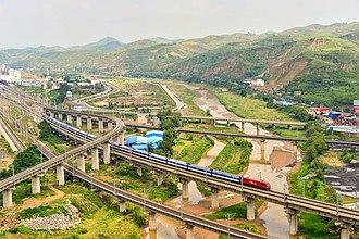 Taiyuan–Zhongwei–Yinchuan Railway - A T70 passenger train from Beijing West to Urumqi North on the Taiyuan-Zhongwei-Yinchuan Railway over the Wuding River in Suide, Shaanxi Province near the intersection with the Shenmu–Yan'an Railway (Photo taken in 2014).