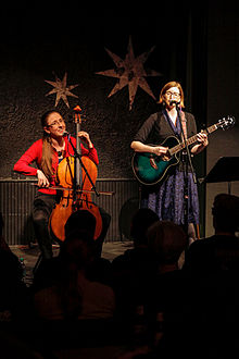 Photograph of the sisters; Aubrey on the left playing a cello and Laser on the right playing a guitar.