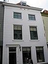 foto van Huis met gepleisterde lijstgevel. Lijst voorzien van tanding en van datering. Moderne 17e-19e-eeuwse winkelpui