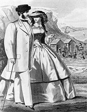 1850s in Western fashion - 1859 fashion plate of both men's and women's daywear, with seabathing in background. He wears the new leisure fashion, the sack coat.
