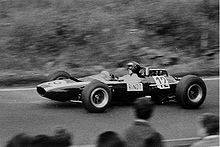 Black-and-white photograph of Jochen Rindt racing in a wingless Cooper Formula One car with his name visibly written on the side of the car