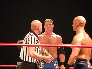 Three adult males standing in a wrestling ring. One is bald wearing a black and white striped shirt holding a championship belt. Another is staring at him wearing blue wrestling gear. The third is doing the same but is wearing black wrestling gear and is bald.