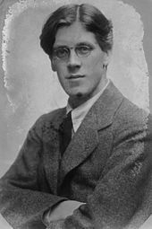 A black and white photograph of a young man wearing glasses