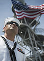 A U.S. Sailor mans the rails aboard the amphibious dock landing ship USS Pearl Harbor (LSD 52) May 25, 2013, as the ship leaves Pearl Harbor, Hawaii, for Samoa, the first mission port for Pacific Partnership 130525-N-SP369-090.jpg