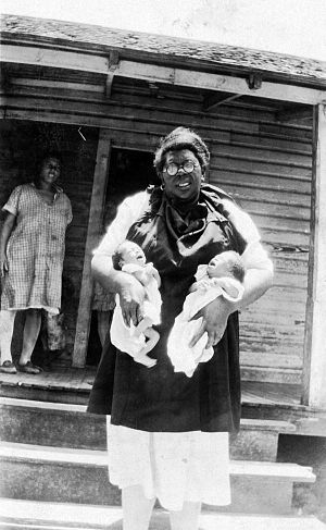 Maternal mortality in the United States - Black and white image of an African-American midwife with glasses holding twins in front of a house, with another African-American woman standing behind her to the left. The photo was taken in Tallahassee, Florida.
