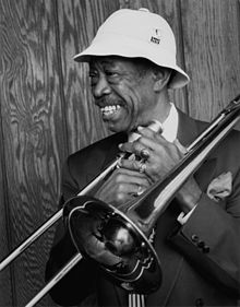 Black and white photography of a smiling black man with a white hat and a dark jacket holding a trombone in front of him with his both hands with wood wall behind.