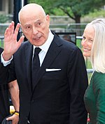 A Caucasian male wearing a black suit and tie with a white collar shirt is seen waving his right hand. He is standing next to a blonde female wearing a green dress.