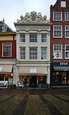foto van Huis Leeuwenburg, op gebeeldhouwde banderol 1707 gedateerd, met een geheel met natuursteen beklede gevel en een barok, rijk gebeeldhouwd hoofdgestel op zware consoles, bekroond door beeldhouwwerk, bestaande uit een ca