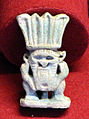 Amuleto in faience a forma di bes, protettore dlele culle dei neonati, 710-690 ac ca, da pietrera di sagrona, a pietre bianche.JPG