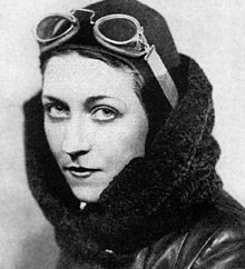 Black and white portrait photograph taken around 1930 of Amy Johnson, wearing aviator attire; googles, leather cap, leather and wool flying jacket