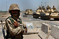An Iraqi Army soldier stands guard duty while Iraqi T-72 tanks pass through a highway checkpoint in Mushahada, Iraq.jpg