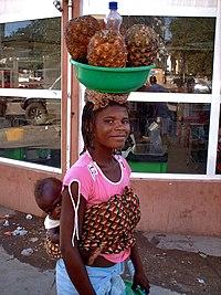 Trabalhadora angolana carregando filho.