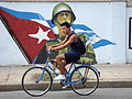 Bicyclist on Street with Nationalist Mural - Cienfuegos - Cuba.jpg