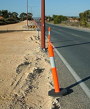 Road traffic control - Traffic Control bollards separating the road from the worksite. Note the chevron signs indicating worksite exit points.
