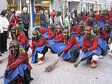 foto que muestra a personas vestidas como brujas con máscaras y escobas desfilando por las calles