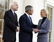 White-haired man in dark suit looks on as gray-haired man in dark suit holds hand and greets blonde-haired woman in medium-colored suit, all in front of a white building.