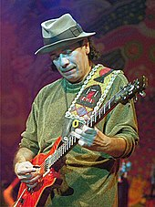 A man wearing a grey hat and a green sweater playing the electric guitar.